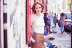 Urban photo of a red haired girl in the summer sun