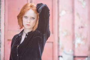 Quirky red head girl in London by red background