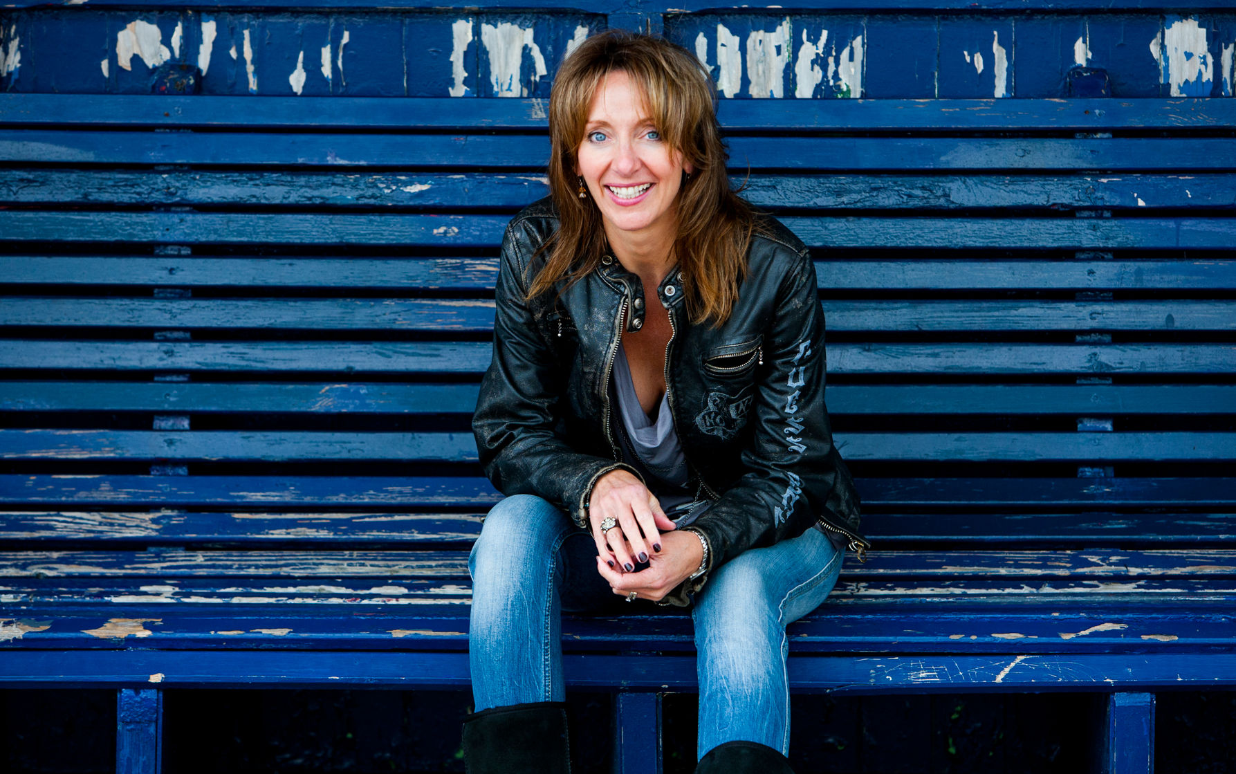 Lady on a blue bench and blue background wearing a black leather jacket smiling to camera