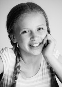 Young actress in black and white smiling to camera for spotlight profile image