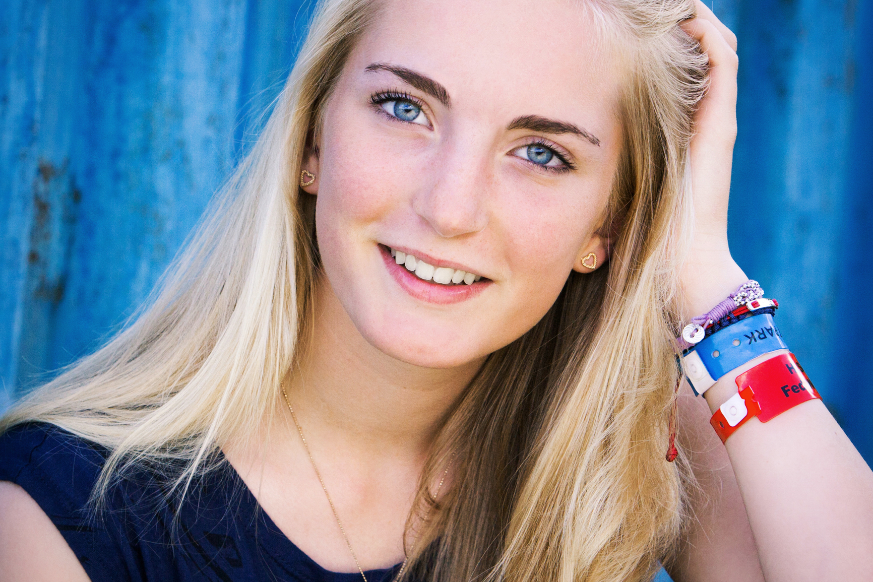 Young sportswoman with blue eyes against a blue background